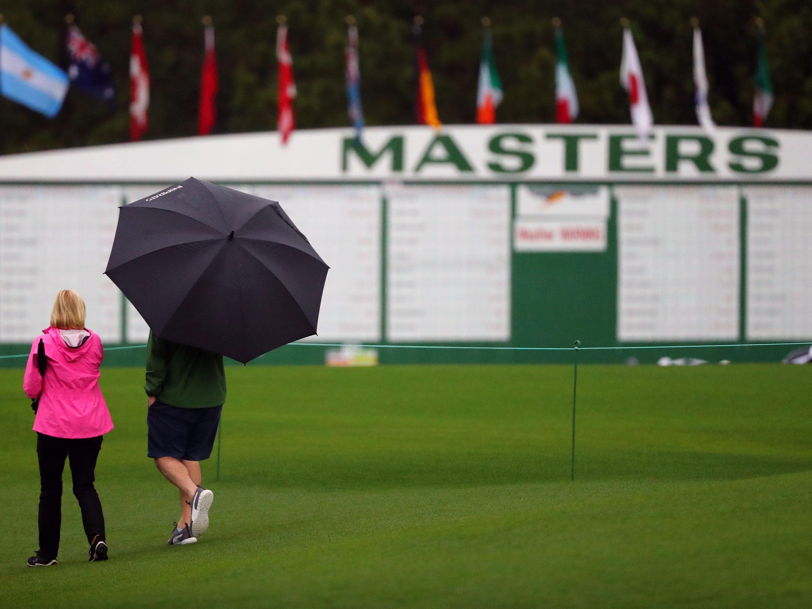 Patrons take the course under a weather warning with rain and the threat of thunderstorms during a practice round for The Masters golf tournament at Augusta National Golf Club.