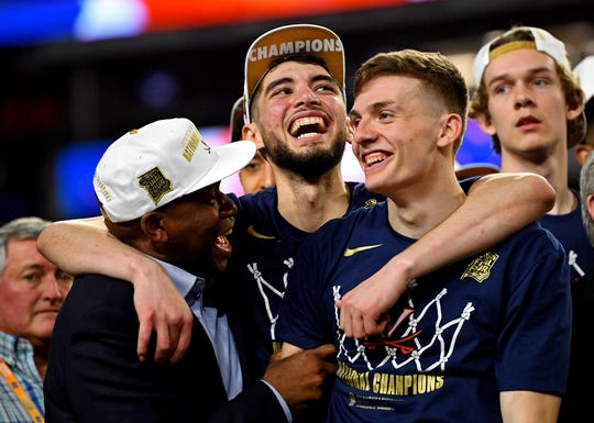 Virginia guards, right, Kyle Guy and Ty Jerome, middle, celebrate after winning the national championship in Minneapolis.
