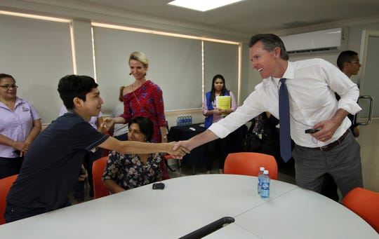 California Gov. Gavin Newsom, right, and his wife, Jennifer Siebel Newsom greet Byron Daniel, 17, a young Salvadoran, who had fled El Salvador due to the harassment of gang members looking to recruit him, during their visit to La Chacra Immigration Center in San Salvador, El Salvador, Monday, April 8, 2019. The Migrant Care Center processes deported migrants.
