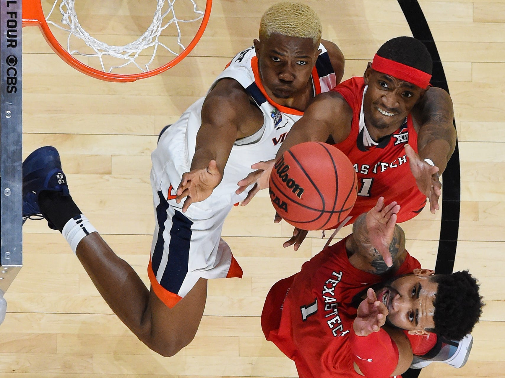 Virginia's Mamadi Diakite and Texas Tech's Tariq Owens (11) and guard Brandone Francis (1) go up for a rebound.