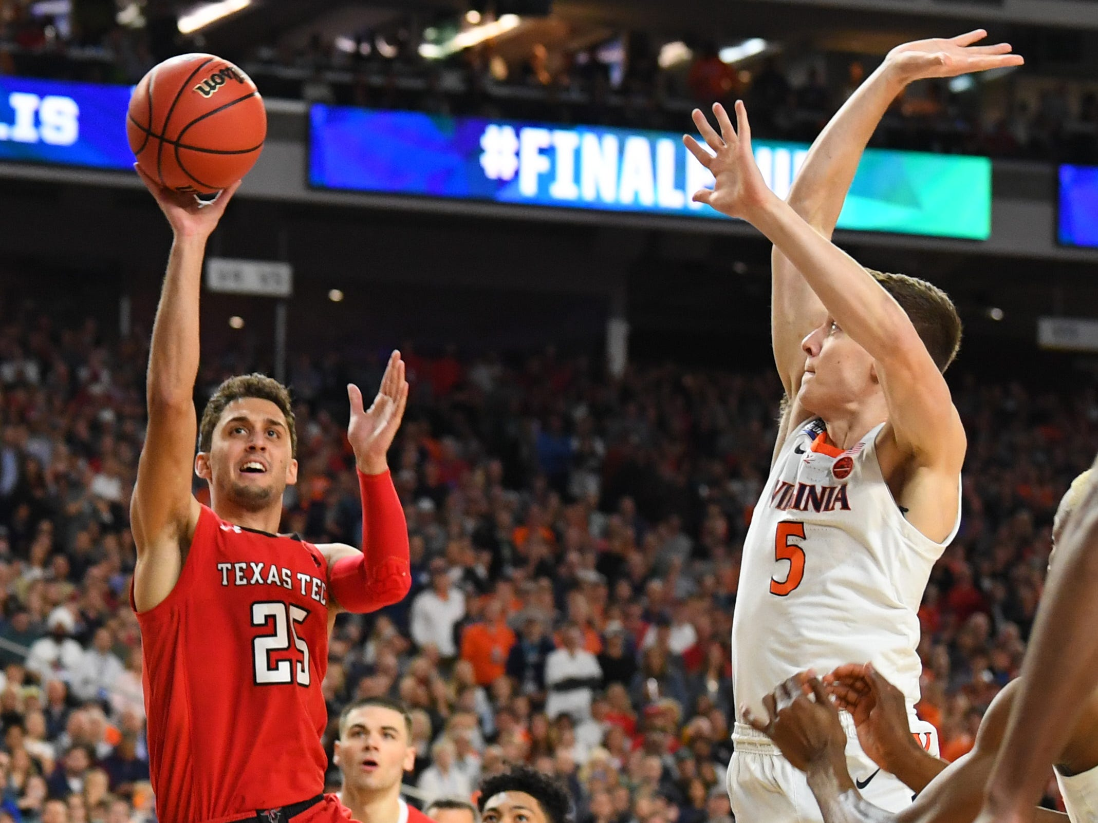 Texas Tech's Davide Moretti (25) shoots the ball defended by Virginia's Kyle Guy in the championship game.