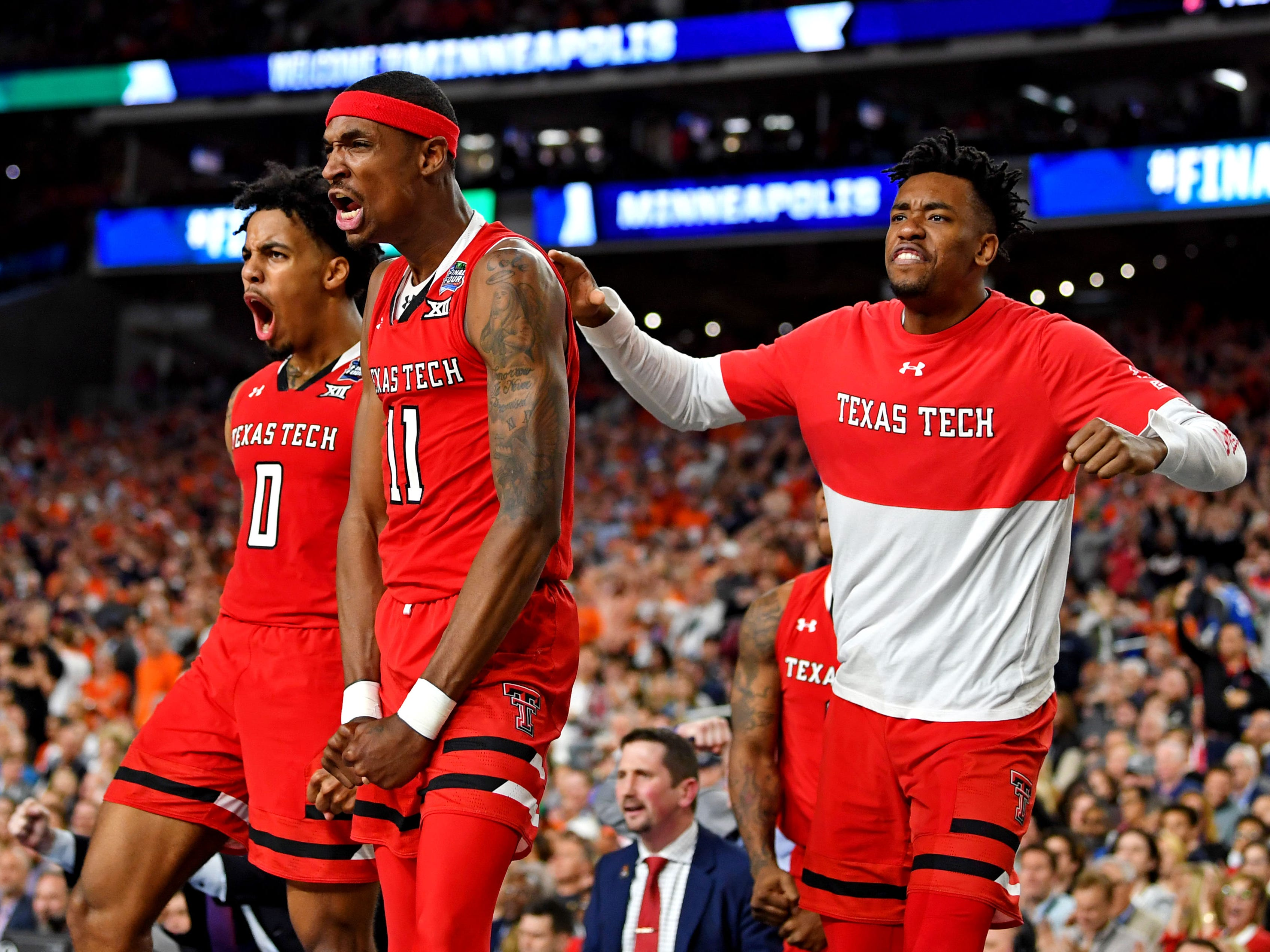 Texas Tech's Tariq Owens (11) and Kyler Edwards (0) react from the bench during the second half against Virginia.