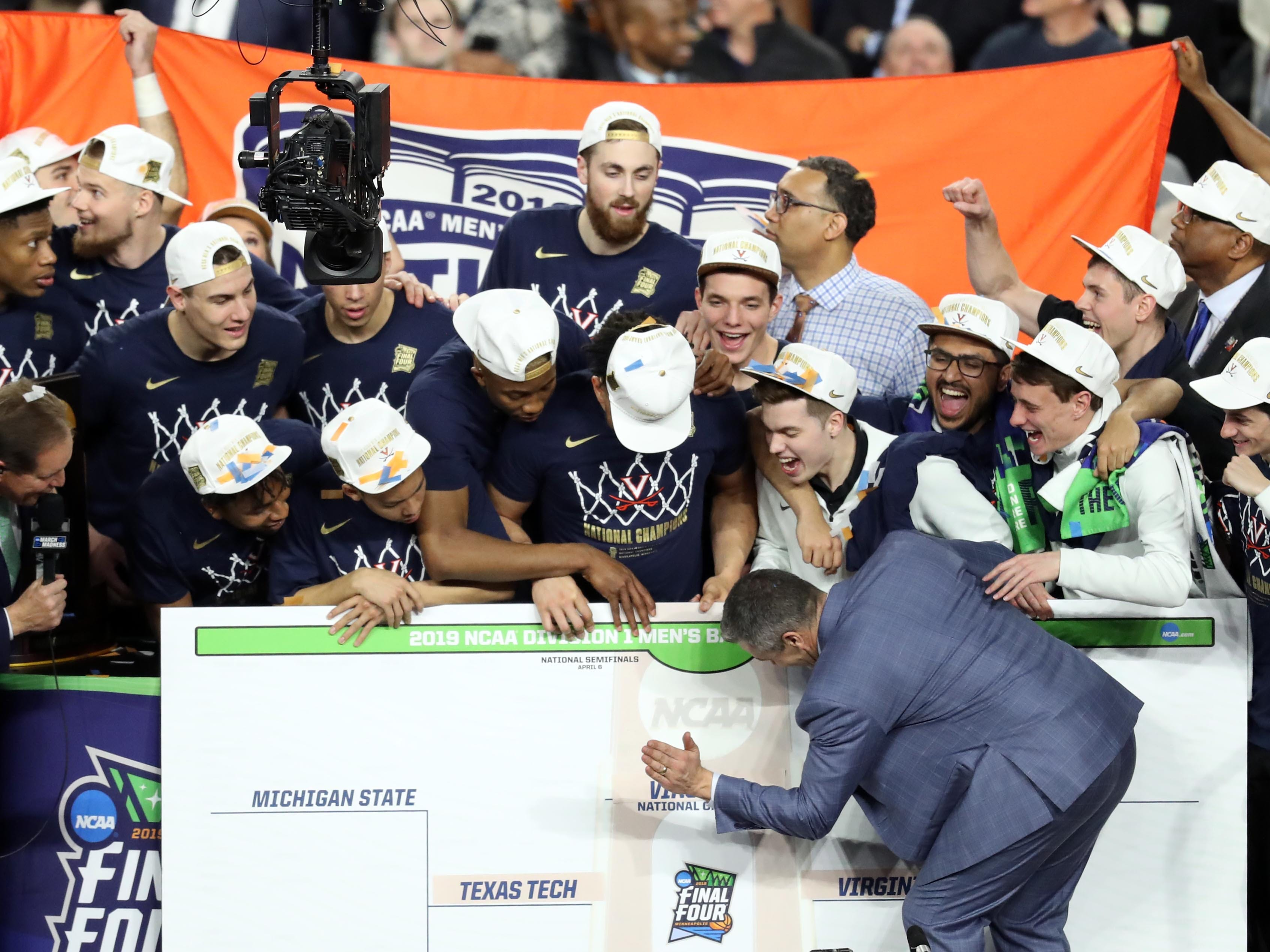 Virginia coach Tony Bennett and players celebrate after defeating Texas Tech  in the championship game.