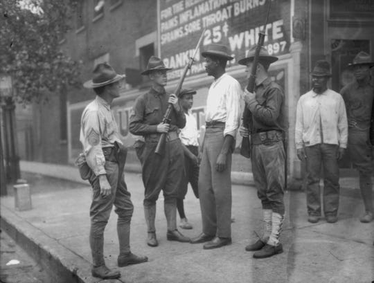 "National Guardsmen, called in by Chicago Mayor 'Big Bill' Thompson after three days of rioting in the summer of 1919, question an African American man. More than 100 years ago, Jamaican writer Claude McKay penned ""If We Must Die"" as a response to violence that year by whites against blacks. (Photo by Jun Fujita/Chicago History Museum/Getty Images)"