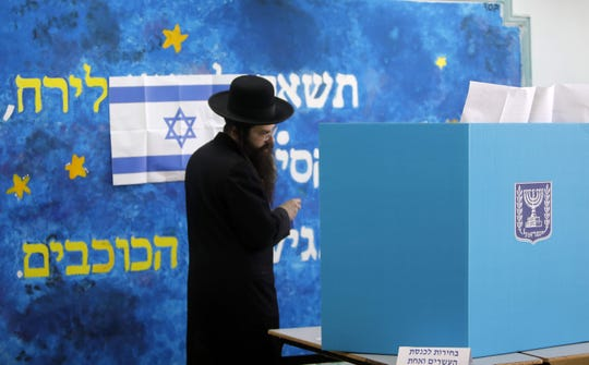 An ultra-Orthodox Jewish man casts his vote during Israel's parliamentary elections on April 9, 2019 in Jerusalem. - Israelis voted today in a high-stakes election that will decide whether to extend Prime Minister Benjamin Netanyahu's long right-wing tenure despite corruption allegations or to replace him with an ex-military chief new to politics.