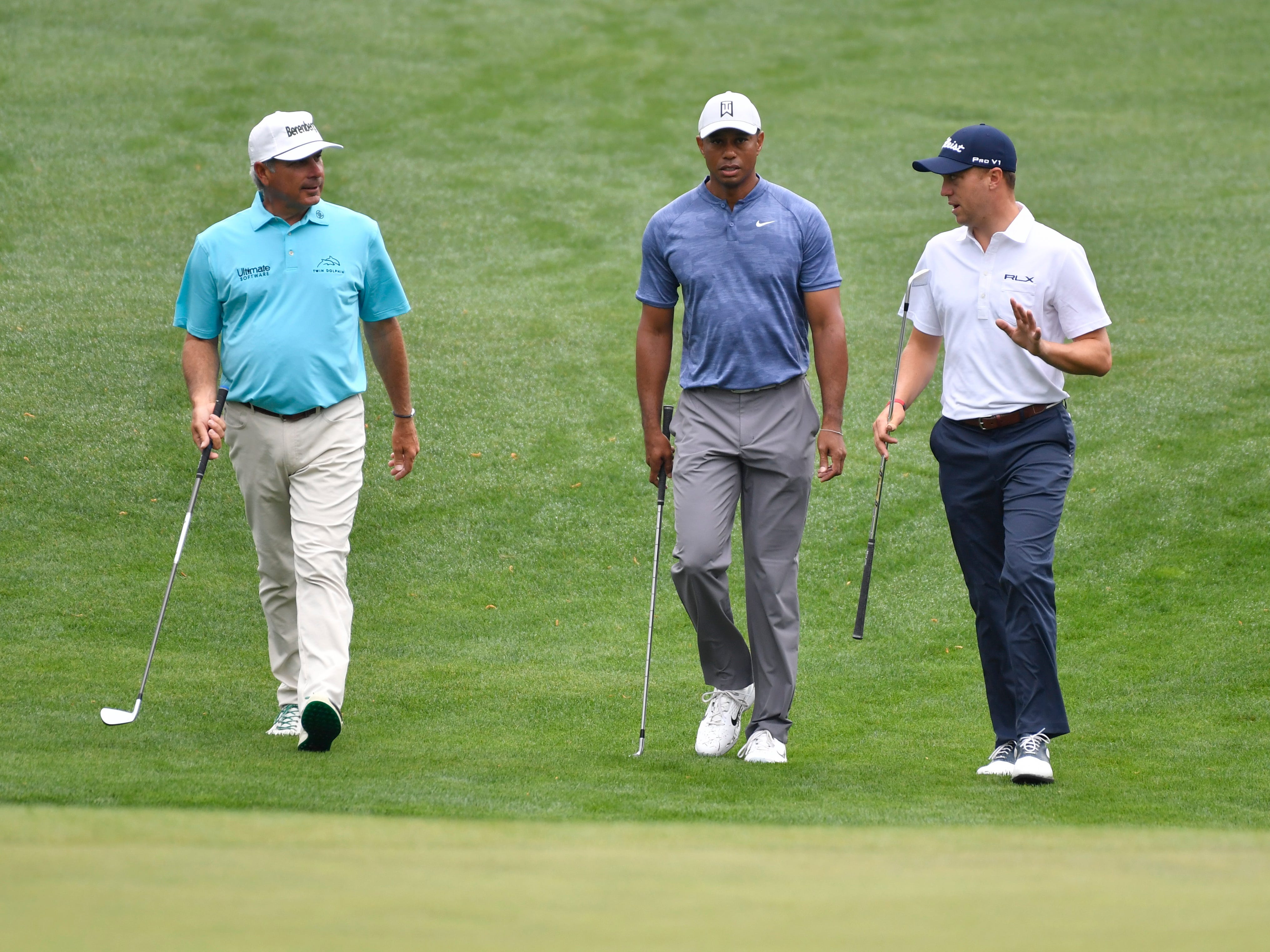 Fred Couples (left) Tiger Woods (center) and Justin Thomas walk to the 16th green during a practice round for the Masters golf tournament at Augusta National Golf Club.