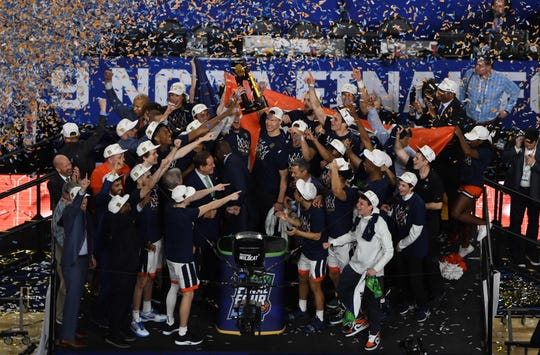 Virginia Cavaliers players celebrate with the trophy after defeating the Texas Tech Red Raiders in the national championship game.