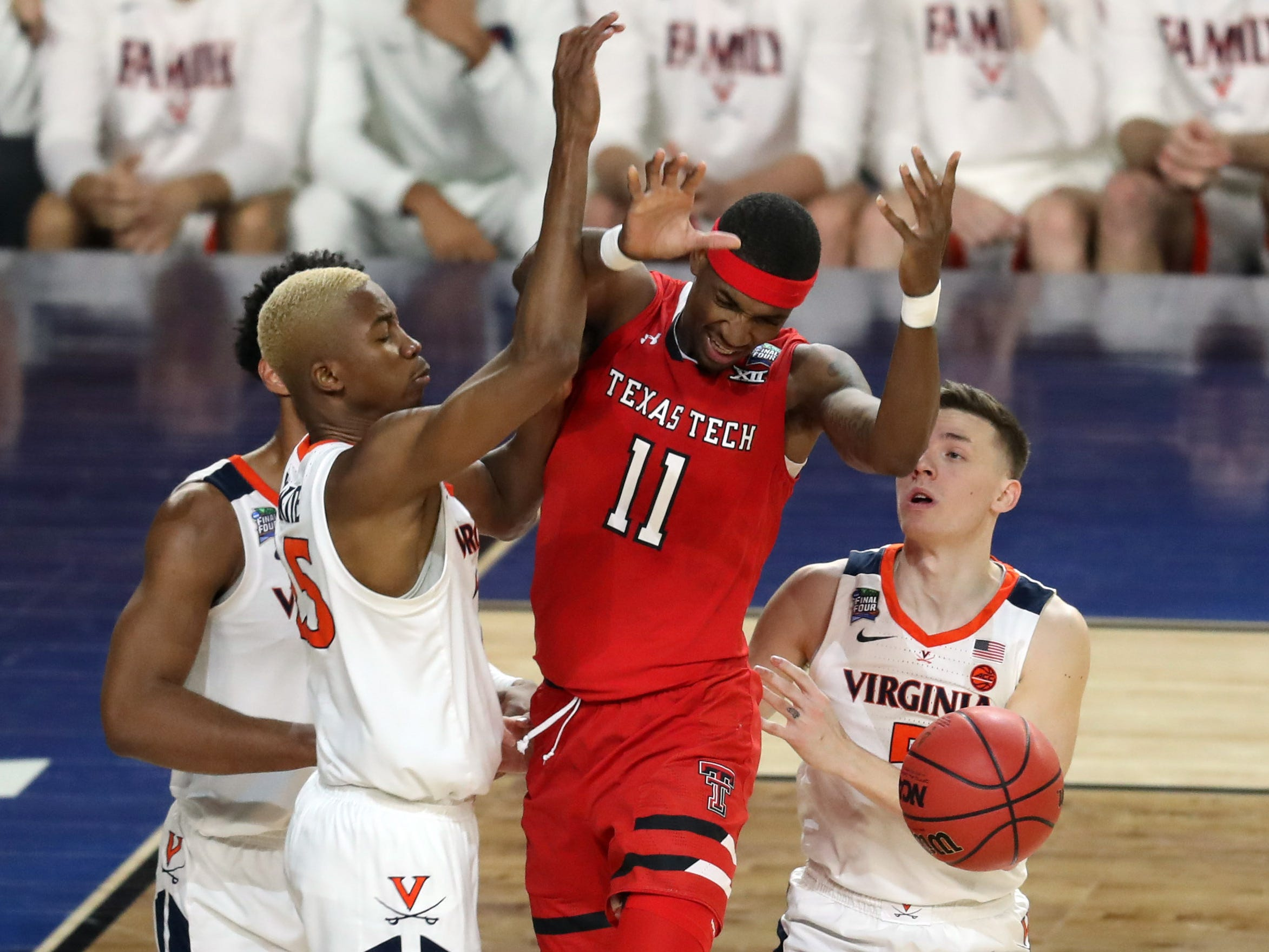 Texas Tech's Tariq Owens (11) loses control of the ball while Virginia's Mamadi Diakite (25) and Kyle Guy (5) defend.