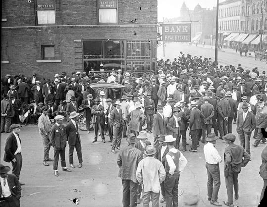 """A crowd in front of a storefront with the sign Bank Real Estate during the 1919 Chicago Race Riots, which began when a white mob drowned a young black man who accidentally swam into the wrong area in Lake Michigan. More than 100 years ago, Jamaican writer Claude McKay penned """"If We Must Die"""" as a response to violence that year by whites against blacks. (Photo by Chicago History Museum/Getty Images)"""
