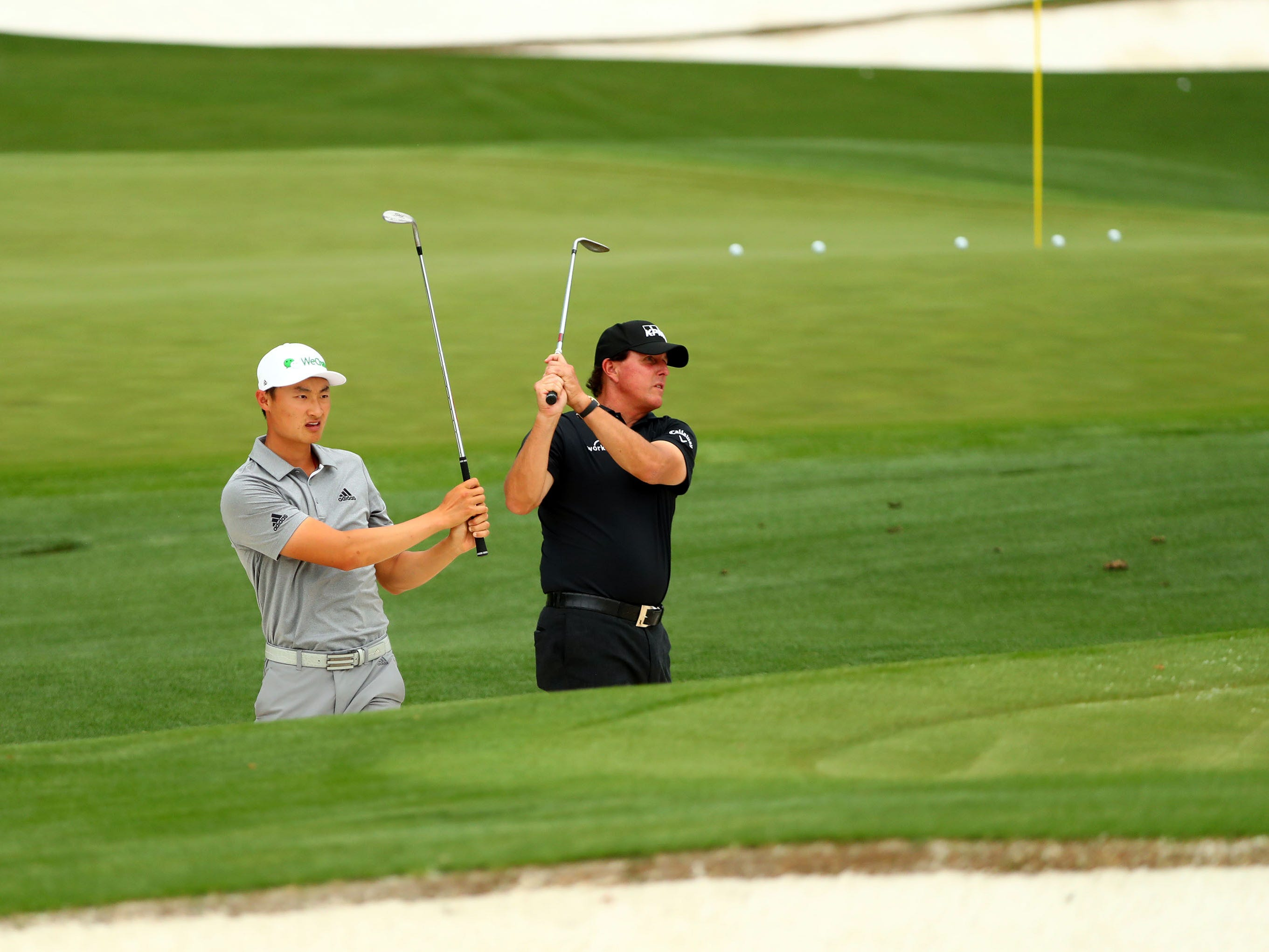 Haotong Li of China and Masters champion Phil Mickelson (right) blast from a bunker on the practice facility during a practice round for the Masters golf tournament at Augusta National Golf Club.