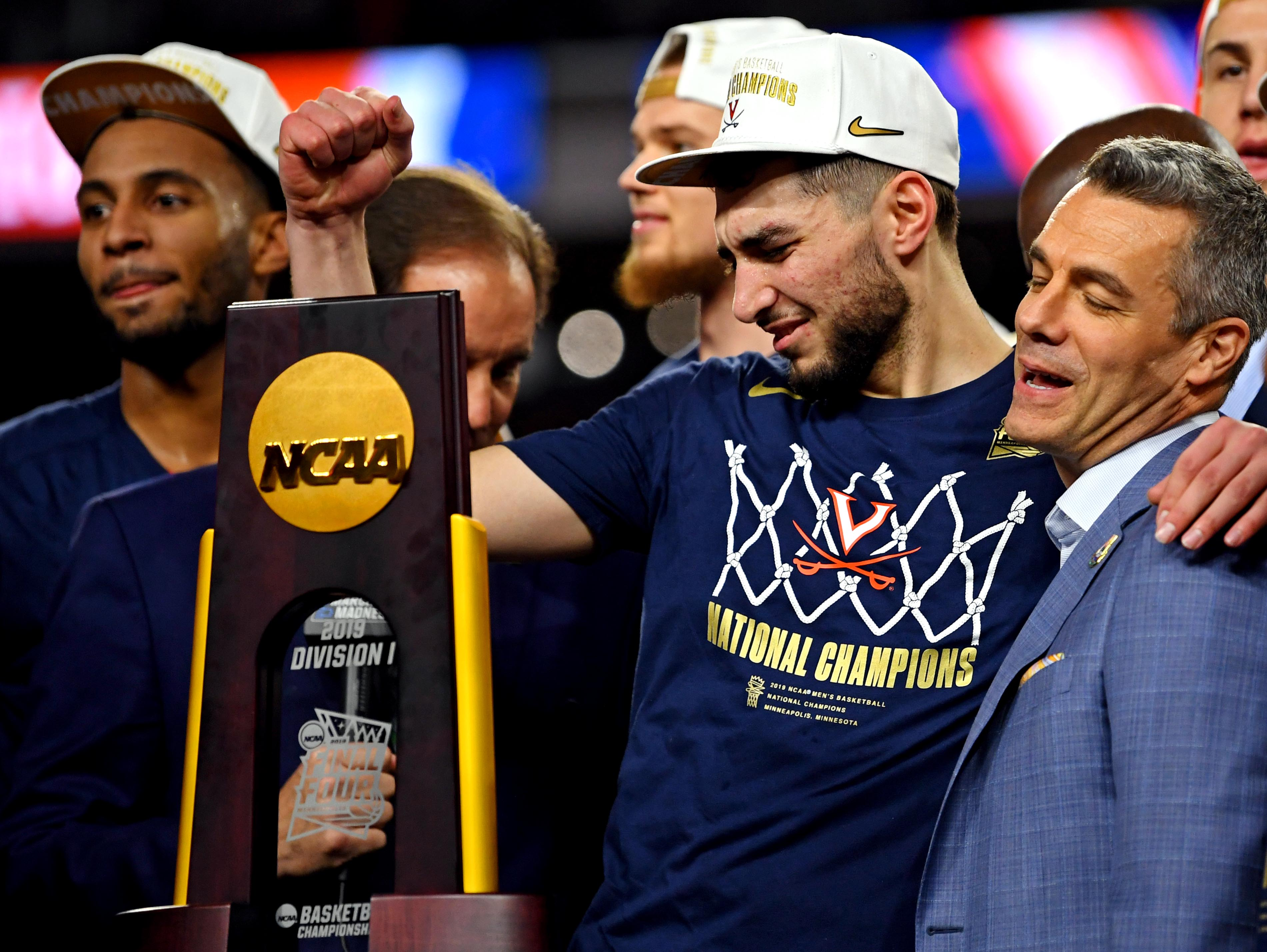 Virginia's Ty Jerome and coach Tony Bennett celebrate after beating Texas Tech in the championship game.