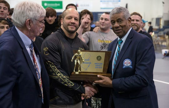 John Stout (center), shown with NJSIAA Executive Director Larry White (right) and NJSIAA Tournament Director Howie O'Neill (left) after Southern won the NJSIAA Group V championship Feb. 10, has resigned as Southern's head wrestling coach