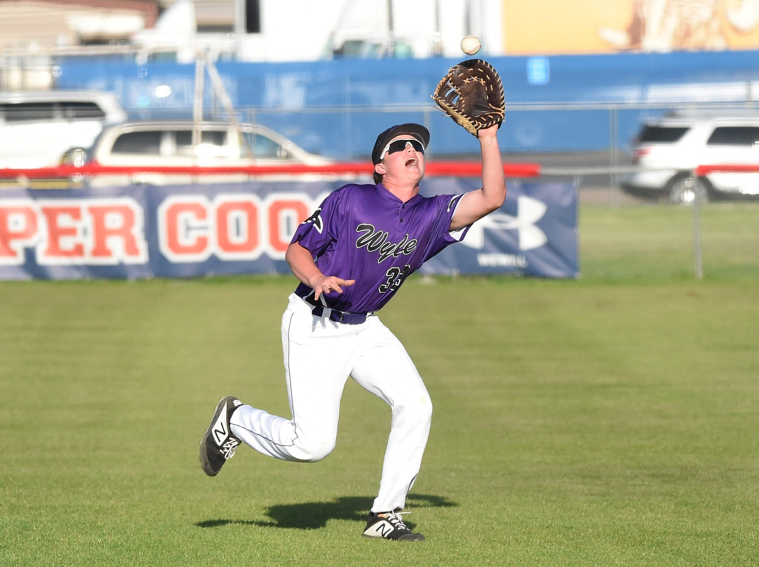 Wylie first baseman Riley Hood (33) looks in a pop up in foul territory against Cooper at Cougar Field on Tuesday, April 9, 2019. The Bulldogs won 11-5.