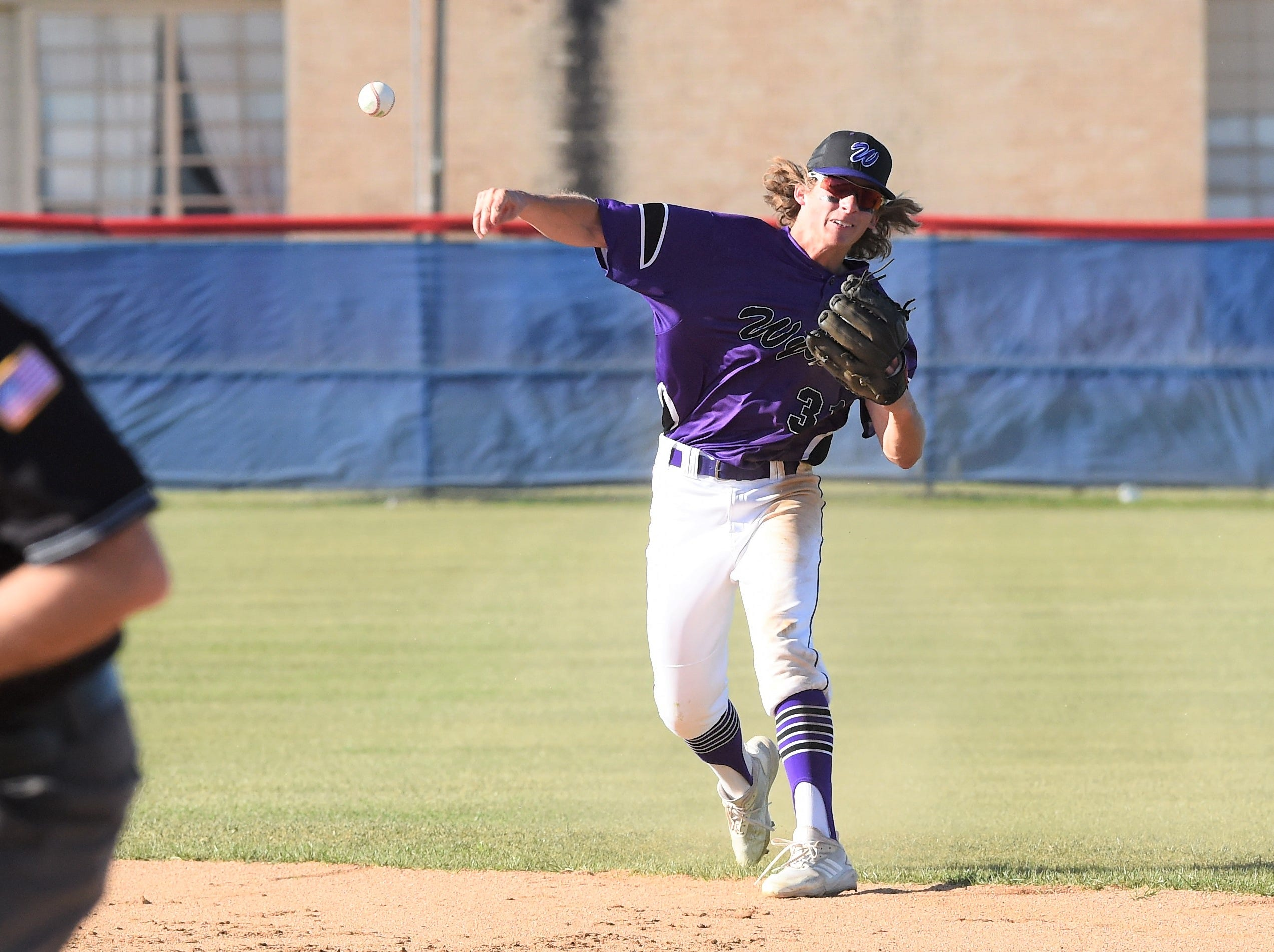 Wylie second baseman Tyler Martin (31) throws to first against Cooper at Cougar Field on Tuesday, April 9, 2019. Wylie pulled out the 11-5 win.