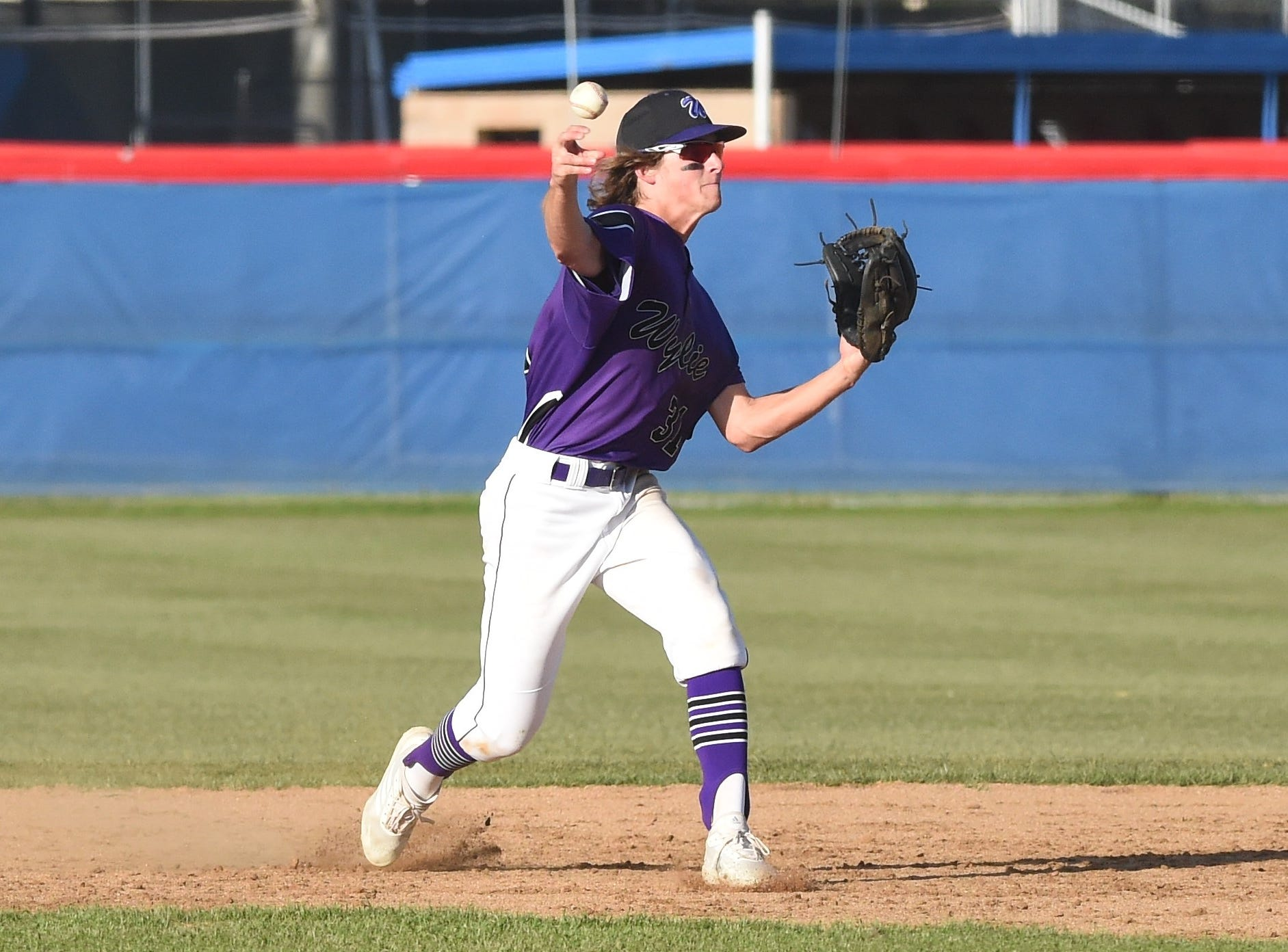 Wylie second baseman Tyler Martin (31) lets go of a throw to first against Cooper at Cougar Field on Tuesday, April 9, 2019. Martin had a hit and two RBIs in the Bulldogs 11-5 win.