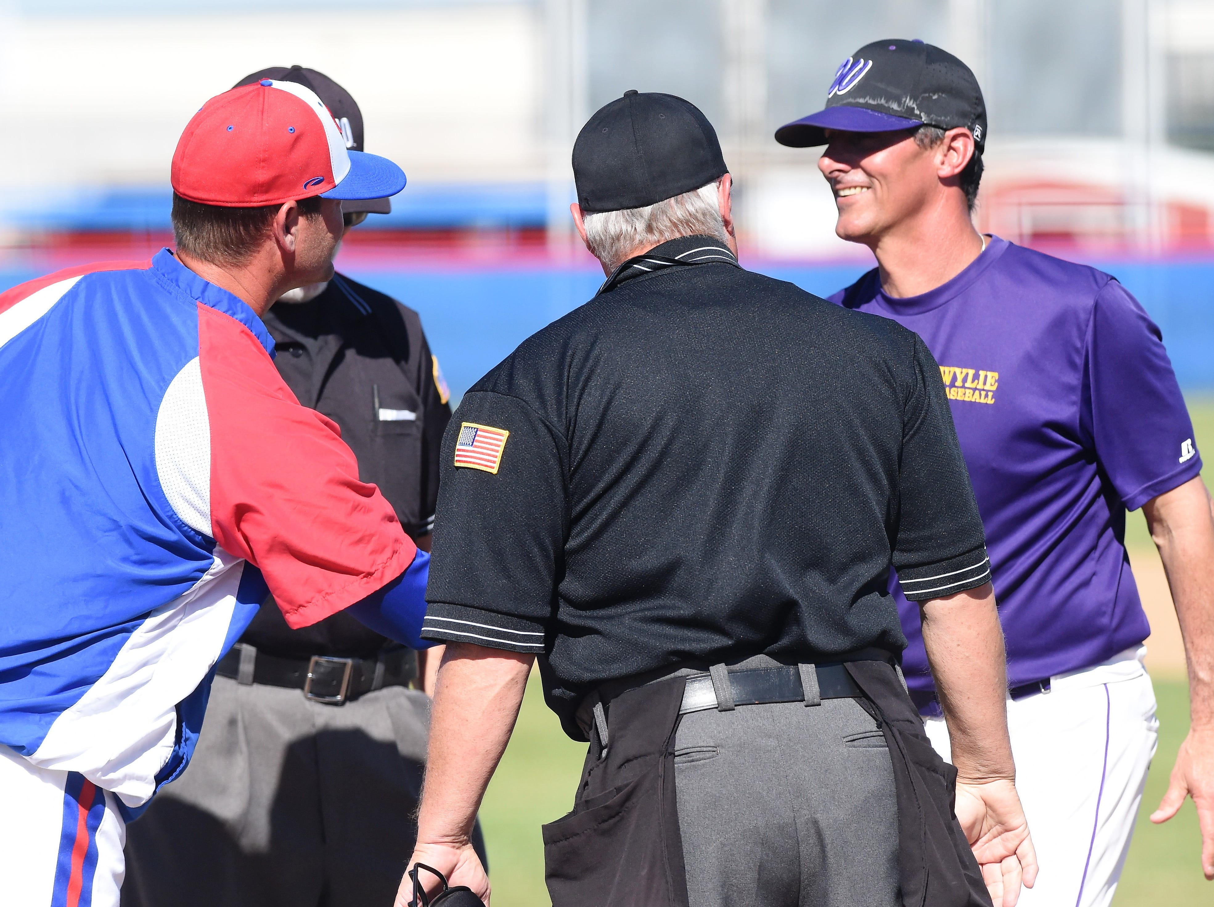 Cooper coach Cody Salyers and Wylie coach Clay Martin shake hands before the game at Cougar Field on Tuesday, April 9, 2019. Wylie pulled out the 11-5 win.