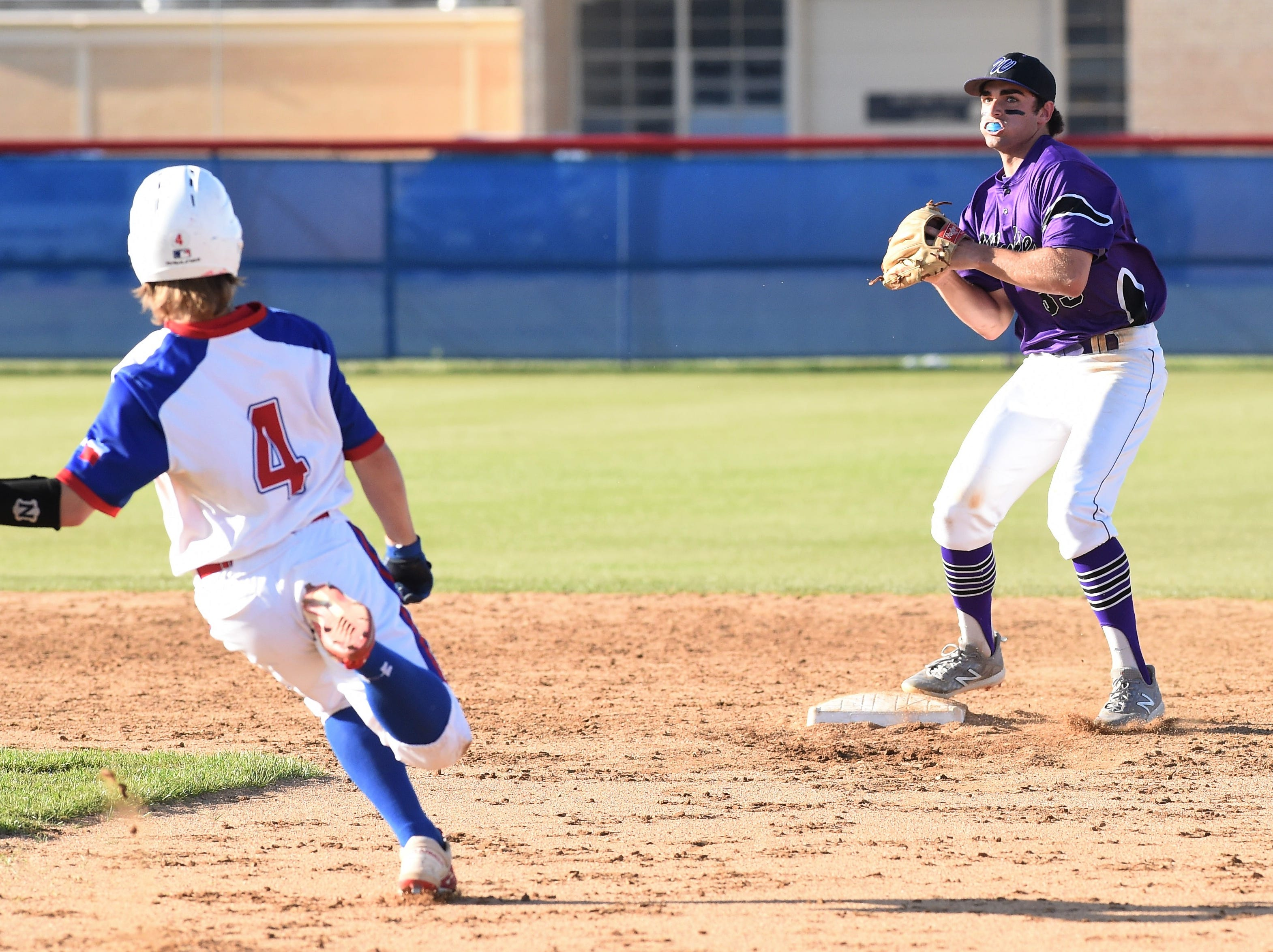 Wylie shortstop Jaxon Hansen (39) steps on second before completing a double play against Cooper at Cougar Field on Tuesday, April 9, 2019. Hansen and the Bulldogs turned three double plays in the 11-5 win.