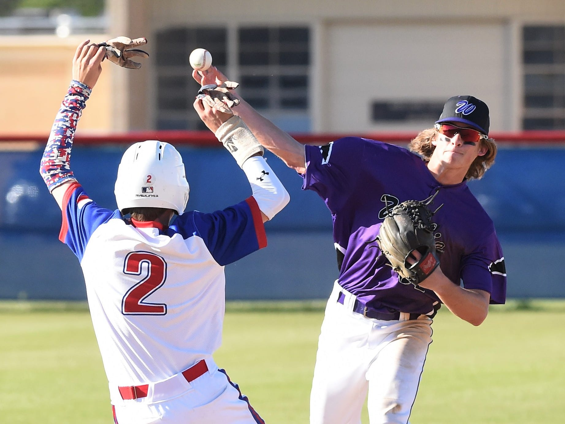 Wylie second baseman Tyler Martin (31) throws around Cooper's Jack Keefer (2) for a double play at Cougar Field on Tuesday, April 9, 2019. The Bulldogs turned three double plays in the 11-5 win.