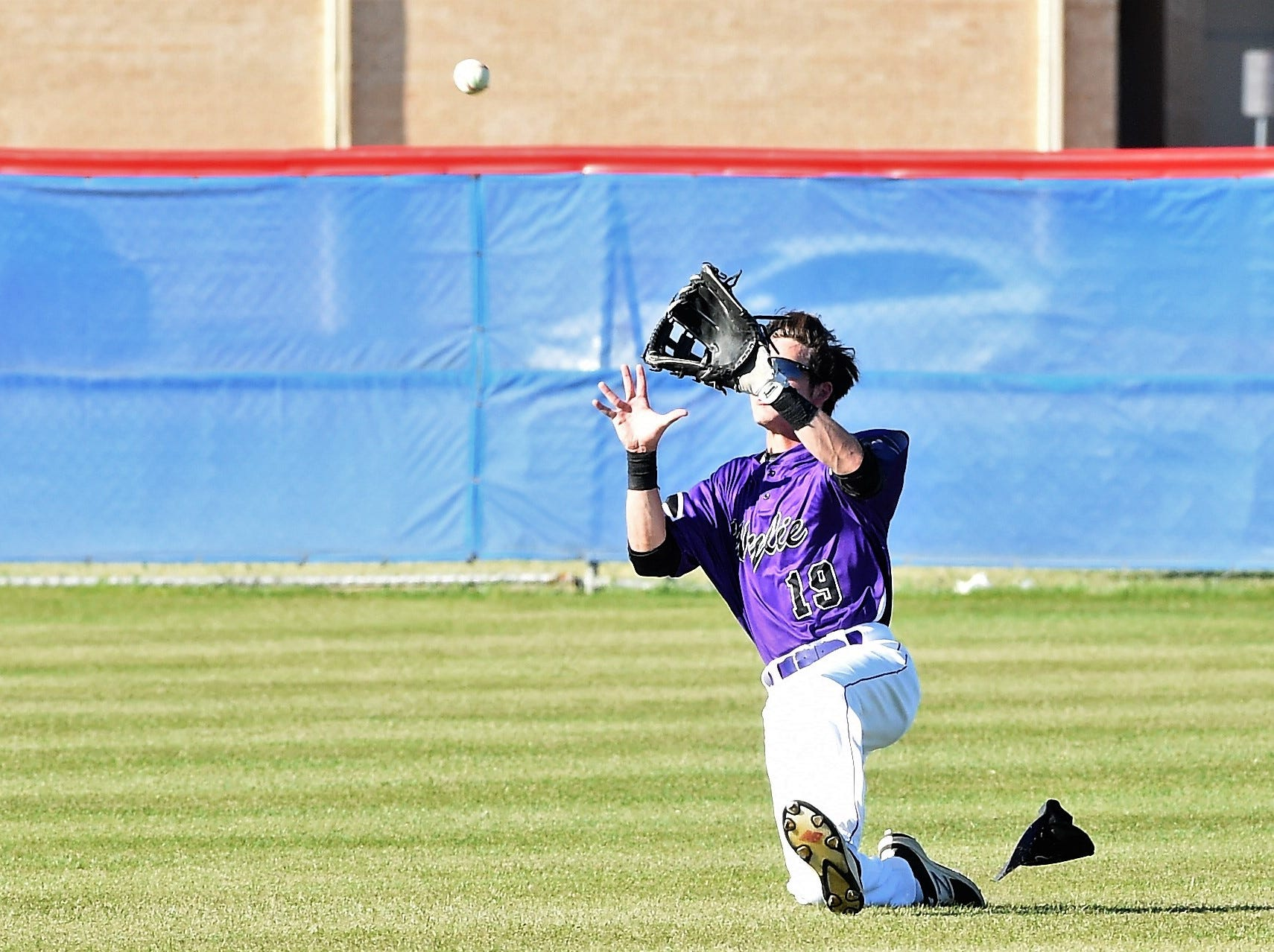 Wylie center fielder Brandon Sanders (19) slides to make the catch against Cooper at Cougar Field on Tuesday, April 9, 2019. Sanders drove in two runs and scored twice in the Bulldogs 11-5 win.
