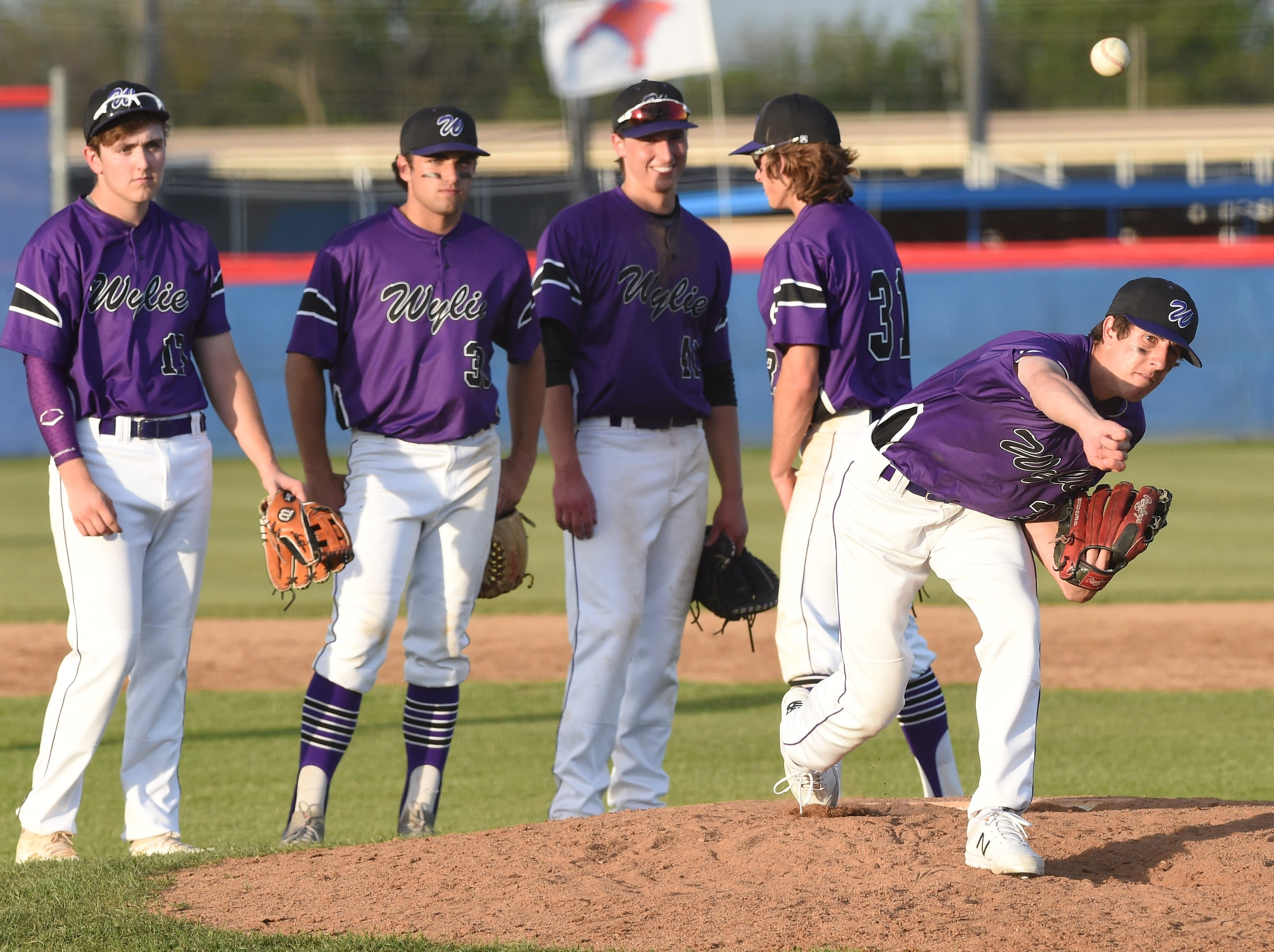 Wylie reliever Cooper Hrbacek (37) warms up with the rest of the infield behind him at Cougar Field on Tuesday, April 9, 2019. The Bulldogs beat Cooper 11-5.