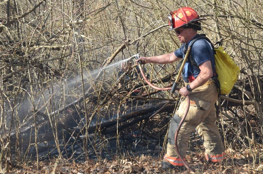 A firefighter carries a bag of water on his back to battle a brush fire.