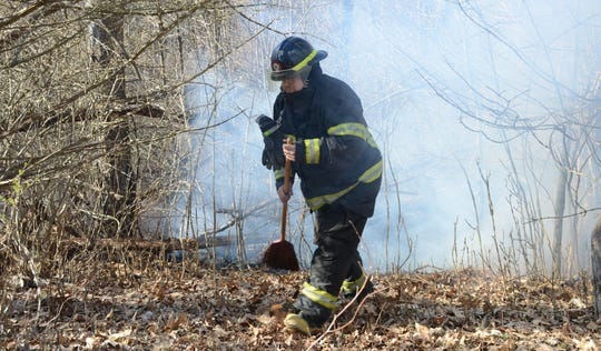 Firefighters use brooms, shovels and rakes to battle brush and field fires.
