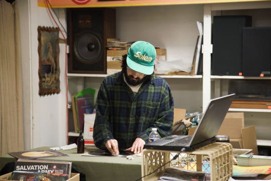 Nick Tassinari, an employee at Angry Mom Records, cleans a record.