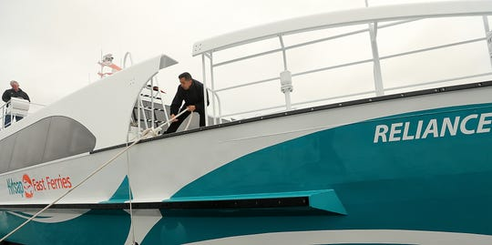 Senior deckhand Lou Trevino pulls the line tight as Kitsap Transit's new fast ferry the Reliance docks in Port Orchard on Wednesday.