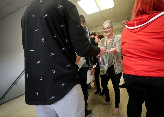 "Dawn Michele Wilson hands out forms and pens to those waiting in the crowded hallway of the Kitsap County Courthouse in Port Orchard during the Public Defender Association, Civil Survival and Kitsap County's ""LFO Reconsideration Day"" on Wednesday."