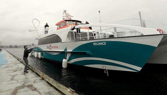 Marine engineer Nick Taylor, left, gets ready to catch the lines tossed by senior deckhand Lou Trevino, center, as Kitsap Transit's new fast ferry the Reliance docks in Port Orchard in April.