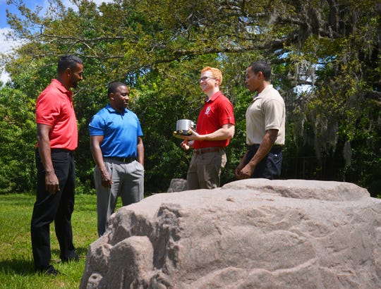 Florida Tech doctorate student Mitchell Solomon holds an infrasound sensor with team members (left to right) Adrian Peter, Anthony Smith and Kaylen Bryan at the River's Edge campus in Palm Bay. The fake landscape rock in the foreground conceals another sensor.