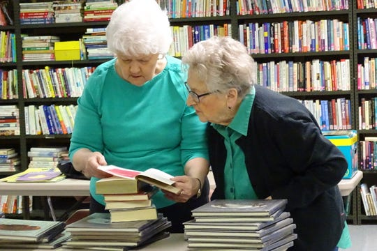 Linda Blicke, left, and Delores Sweeney examine a donated book as the Friends of the Bucyrus Public Library prepare for their annual spring sale on Wednesday. The sale starts Thursday.