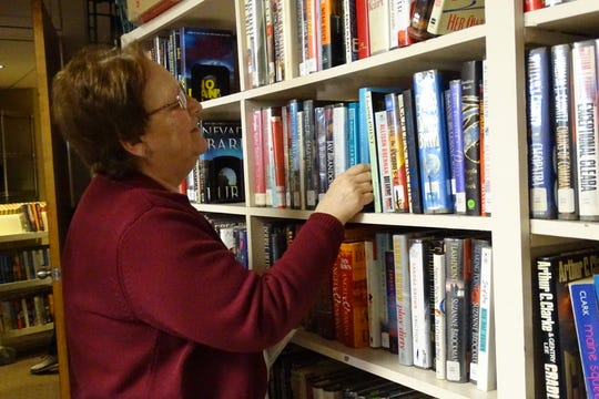 Bev Whaley of Bucyrus shelves books in the fiction room as the Friends of the Bucyrus Public Library prepare for their annual spring sale on Wednesday. The sale starts Thursday.