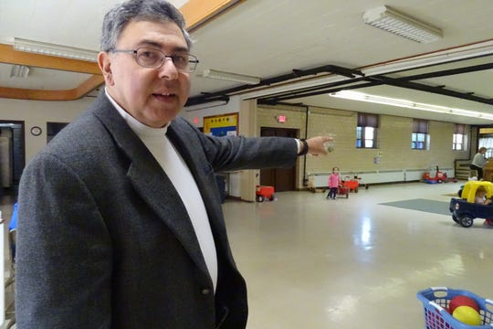 The Rev. Ash Welch points to where emergency cots are stored under a stage in St. Paul United Methodist Church in Galion. The church is a primary emergency shelter.