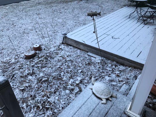 A dusting of snow covers the deck and lawn of a home in South Burlington early Wednesday morning, April 10, 2019. Winter weather returned to Vermont after a short respite.