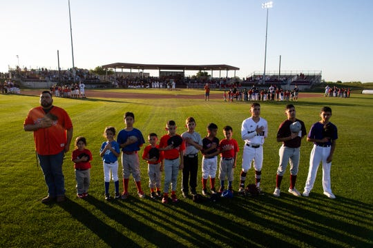 Little league players join Robstown and Sinton for the national anthem at Gene Kaspryzk FIeld, in Sinton on Thursday, April 9, 2019.