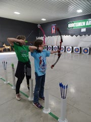 Alyssa Balusik, left, and Bree Carter, right, practice their aim during archery practice on Tuesday. Carter was named state champion for elementary girl's archery in 2019.