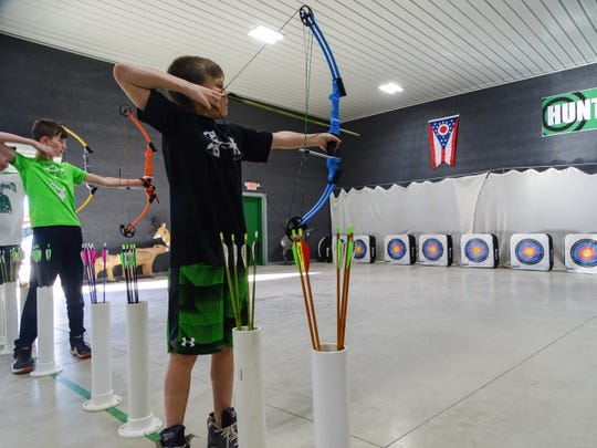 Chad Easterday prepares to release his arrow during the elementary student practice on Tuesday. His mom says that archery has helped him slow down and focus.