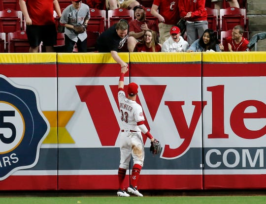 Cincinnati Reds right fielder Jesse Winker (33) fist bumps with a fan in the right field stands after the top of the eighth inning of the MLB National League game between the Cincinnati Reds and the Miami Marlins at Great American Ball Park in downtown Cincinnati on Tuesday, April 9, 2019. The Reds tallied their second win of the season, 14-0, over the Marlins.