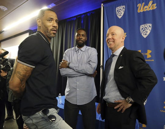 Mick Cronin, right, chats with Cincinnati and NBA star Kenyon Martin, left, and Ronald Allen, who played for Cronin at Cincinnati from 2005 to 2007, after Cronin was introduced as the UCLA's new head basketball coach at a news conference on the campus in Los Angeles Wednesday, April 10, 2019.