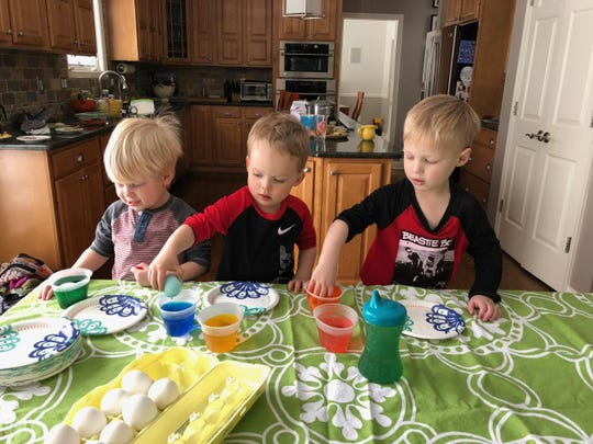 Four-year-old Leo Lipschutz, center, plays host to a pair of friends at a recent an egg-dyeing part.