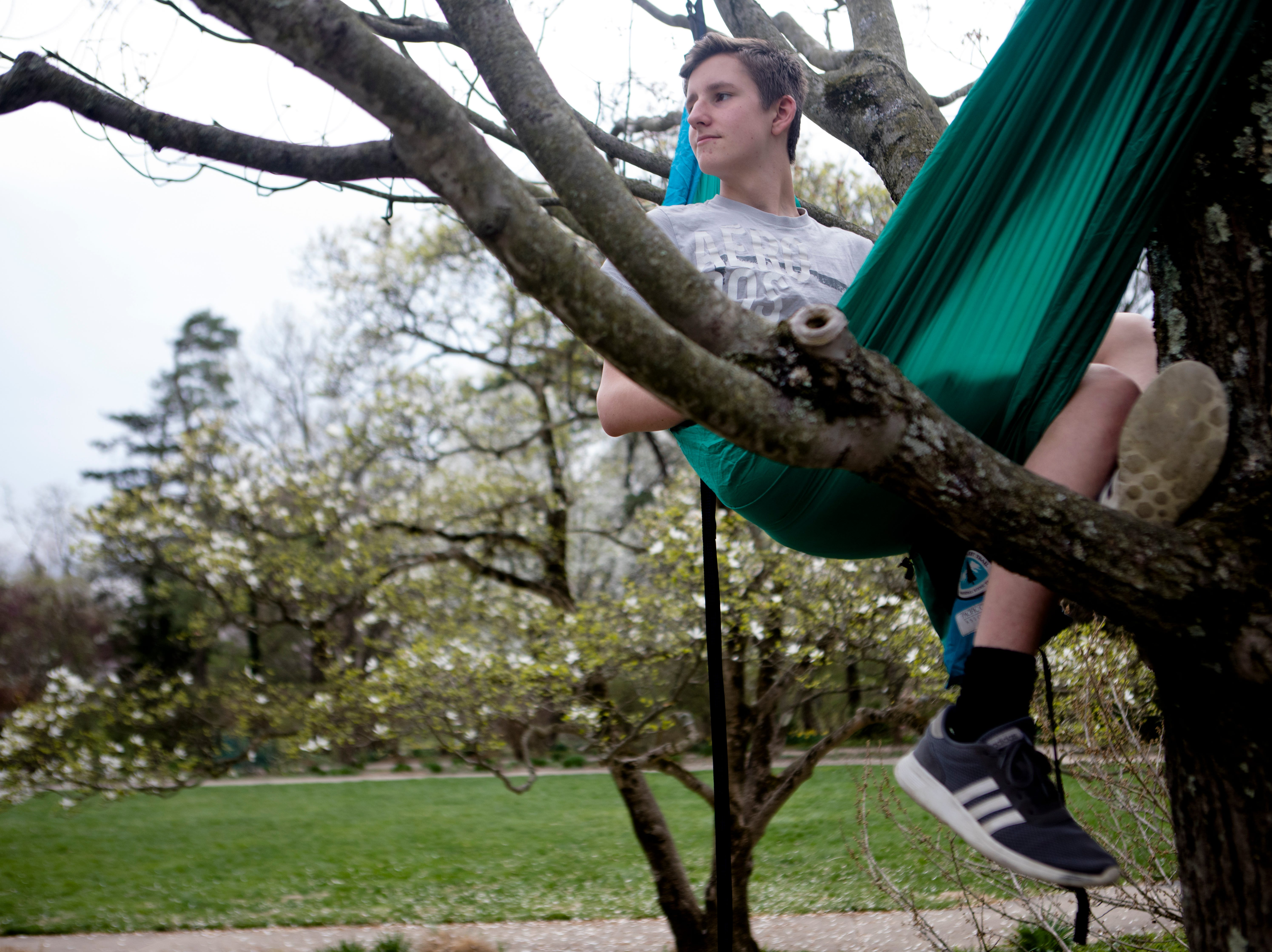 Drew Schirmer, 15, sits in a hammock at Ault Park in Hyde Park on Wednesday, April 10, 2019.