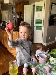 Leo Lipschutz, 4, admires a newly dyed egg. Nearby, on the floor, his 11-month-old sister Goldie is more interested in an empty package.