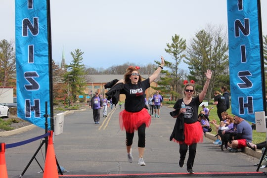 Participants from the 2018 Run 4 Kids celebrate crossing the finish line.