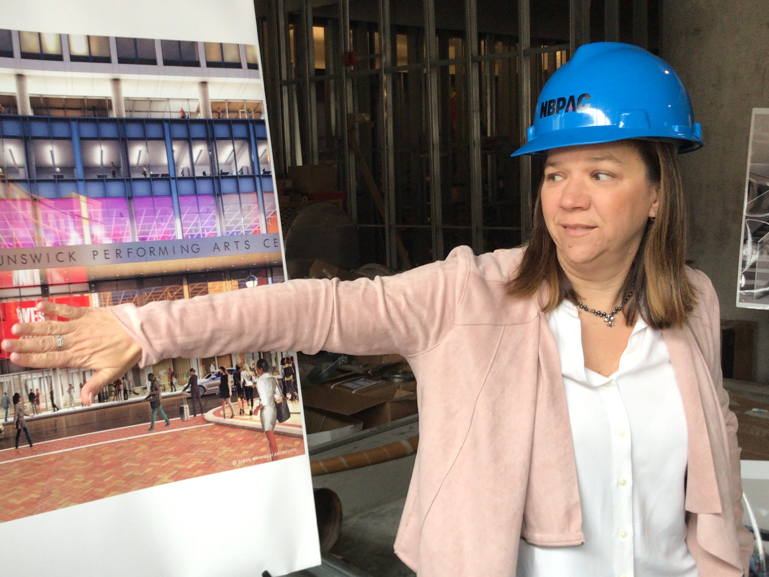 DEVCO Vice President Merissa A. Buczny  points out a digital billboard that be within the soon-to-open New Brunswick Performing Arts Center.