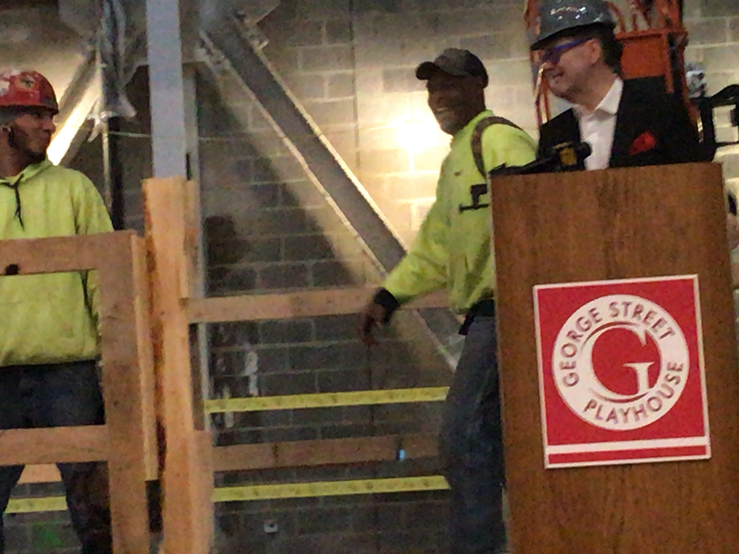 George Street Playhouse Artistic Director David Saint jokes with construction workers at the emerging New Brunswick Performing Arts Center, scheduled to open in September. The Playhouse's inaugural season in the new venue will begin in October.