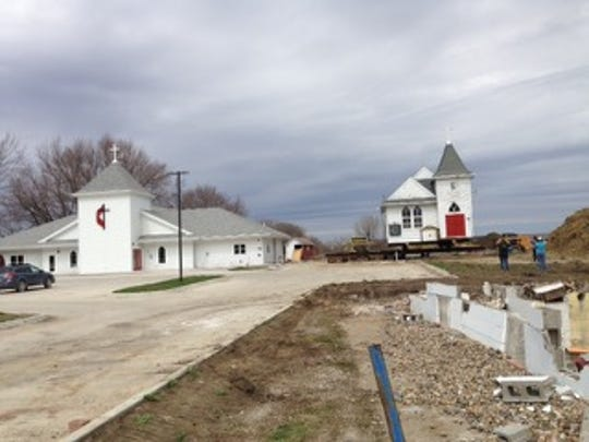 The Maple Grove Methodist Church structure sits on a wheeled platform after being moved away from expanding Ashworth Road and next to the newer worship center.