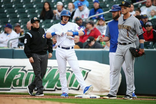 The Iowa Cubs' Ian Happ pulls off his batting gloves while standing on first base during the I-Cubs' home opener against the New Orleans Baby Cakes on Tuesday, April 9, 2019, at Principal Park in Des Moines.