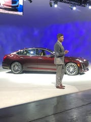 Cadillac Executive Director of Global Design Andrew Smith stands near the 2020 CT5 luxury sedan in Detroit.