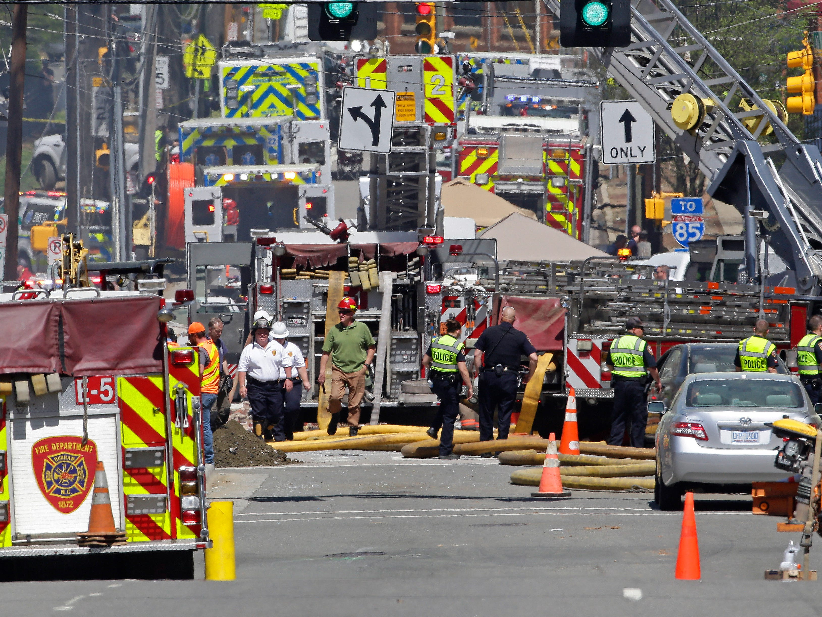 Firefighters and emergency personnel work the scene of an explosion and building fire in downtown Durham, N.C., Wednesday, April 10, 2019.